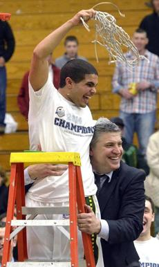 Siena's Steven Cruz is hugged by coach Jimmy Patsos after the Saints won the College Basketball Invitational title.